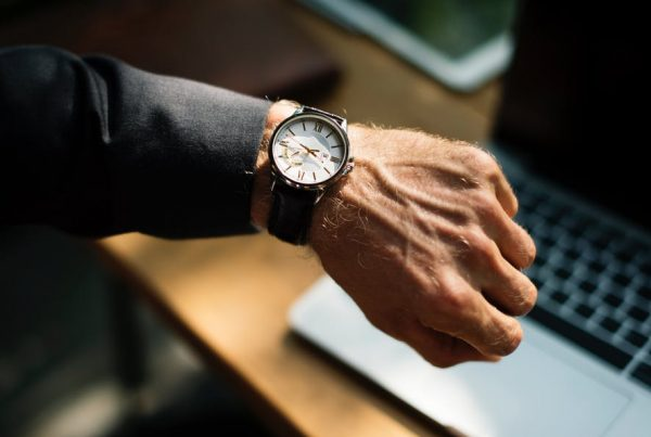 Man looking at watch to make the most of the hours